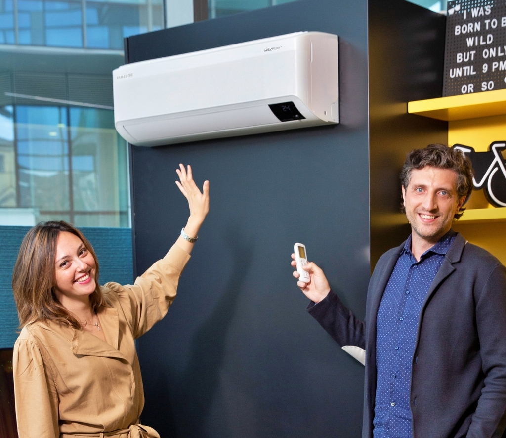 This photo provided by Samsung Electronics Co. on Monday, shows the company's employees introducing Samsung's wind-free air conditioner at its showroom in Italy. (Samsung Electronics Co.)