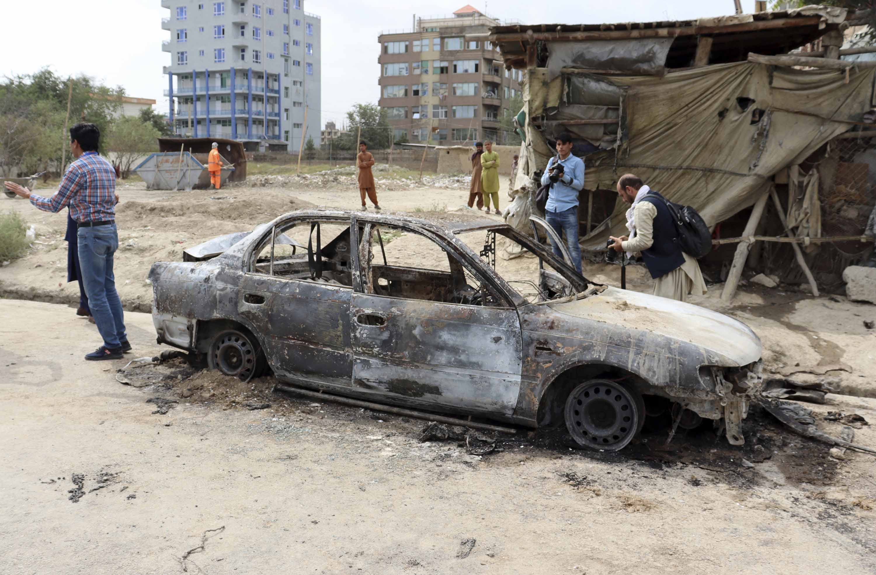 Journalists take photos of a destroyed vehicle where rockets were fired from, in Kabul, Afghanistan, on Monday, August 30.