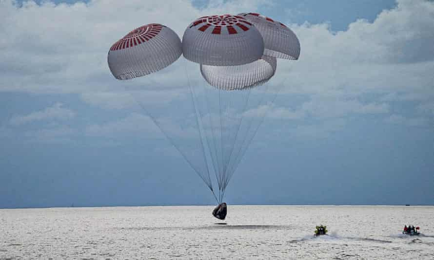In this image taken provided by SpaceX, a capsule carrying four people parachutes into the Atlantic Ocean on 18 September.
