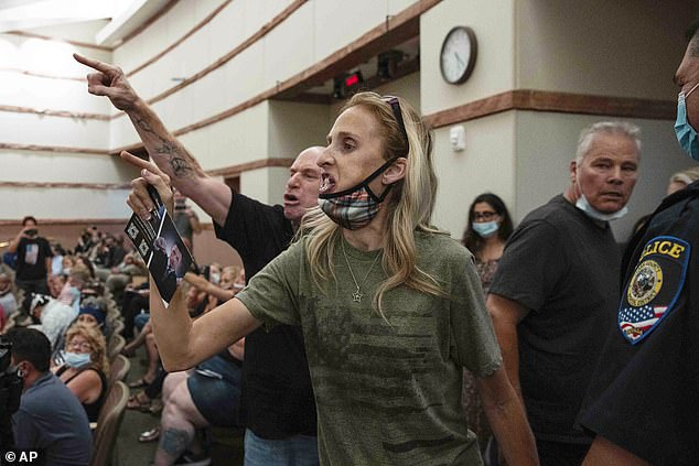While parents are divided on Covid safety measures, the majority agree that kids should be back in classrooms this fall. Pictured: Parents protest a mask mandate in Las Vegas, Nevada, August 12, 2021