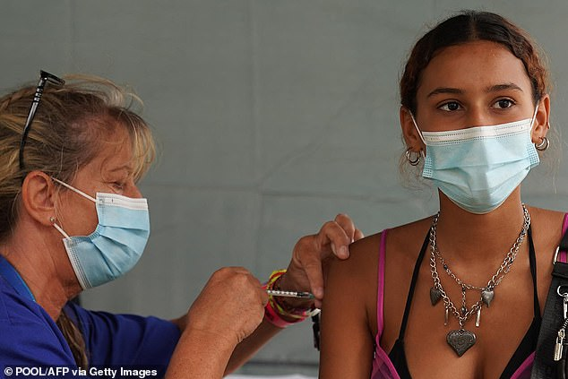A festival-goer is pictured getting an injection from a nurse during a walk-in Covid-19 vaccination clinic at Reading Festival in Berkshire on August 26