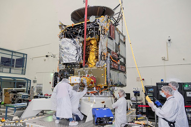 Engineers at NASA's Jet Propulsion Laboratory in Southern California work to integrate Hall thrusters into the agency's Psyche spacecraft in this July 2021 photo. One of the thrusters is visible on the side of the spacecraft beneath a red protective cover