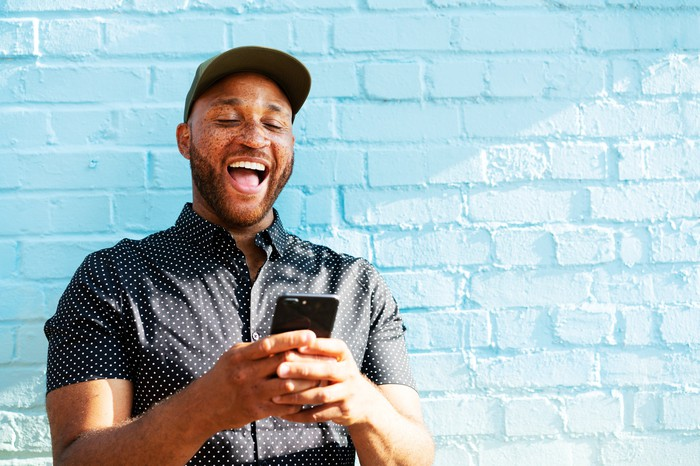 A person appears to be very happy with something they see on their smartphone.