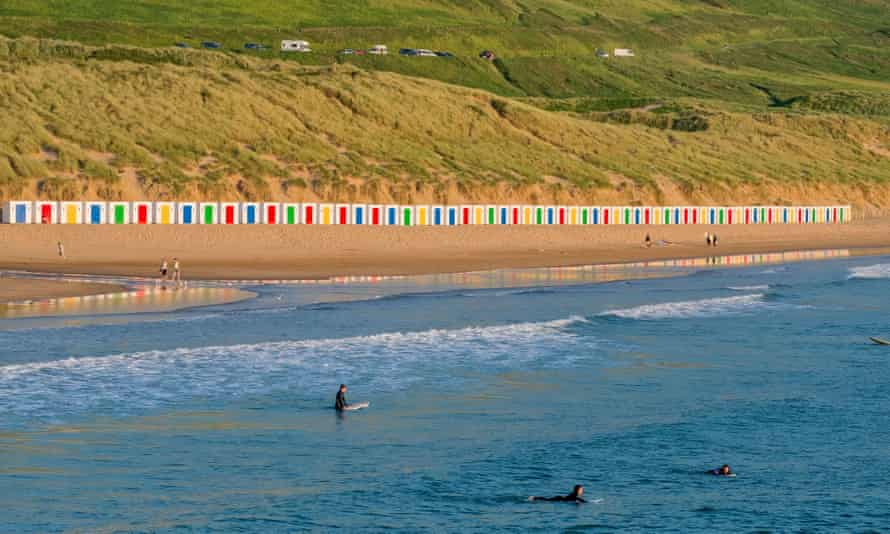 Saunton Sands beach with sand dunes and a line of colourful, painted beach huts on the beach in Devon
