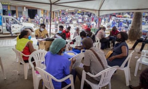 People wait to receive coronavirus vaccinations at a streetside vaccination tent in downtown Kampala, Uganda.