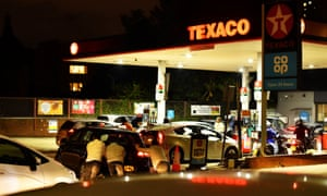 People pushing as a car, which has run out of petrol, at a Texaco fuel station in south London, September 26, 2021.