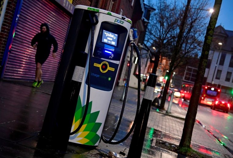 FILE PHOTO: A man runs past a BP (British Petroleum) EV (Electric Vehicle) charge point in London, Britain, January 30, 2021. Picture taken January 30, 2021. REUTERS/Toby Melville/File Photo