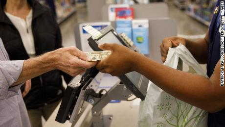 A customer hands cash to an employee while making a purchase at a Walmart location in Burbank, California on November 16, 2017.