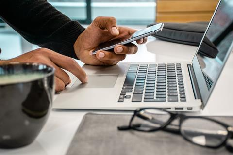 Man working on laptop with phone in hand