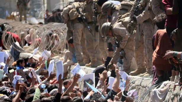 Afghans struggle to reach the foreign forces to show their credentials to flee the country outside the Hamid Karzai International Airport
