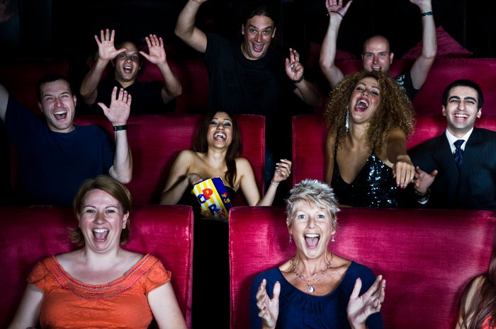 A crowd of people in a movie theater appear excited.