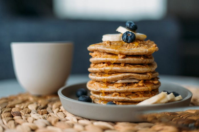Breakfast morning pancakes garnished with blueberries, sliced bananas, and syrup.