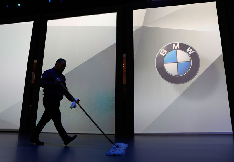 © Reuters. A worker sweeps up the floor in preparation for a BMW press conference at the Los Angeles Auto Show in Los Angeles