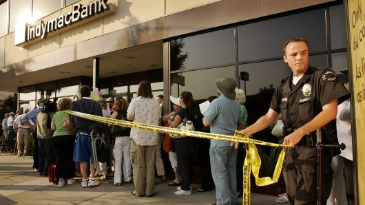 A Los Angeles Police Officer uses yellow tape to cordon off an area for customers with names on a list waiting to enter the IndyMac Federal Bank branch in Encino in July, 2008.