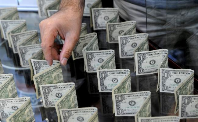 © Bloomberg. An employee arranges US dollar notes in the store display of a foreign currency trader in Tehran, Iran. Photographer: Ali Mohammadi/Bloomberg