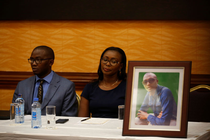 © Reuters. Tom Kabau and Esther Kabau-Wanyoike the brother and sister of Kenyan George Kabau who died in the Ethiopian Airlines crash sit next to his picture during a news conference where their lawyers announced they plan to file a wrongful-death lawsuit against