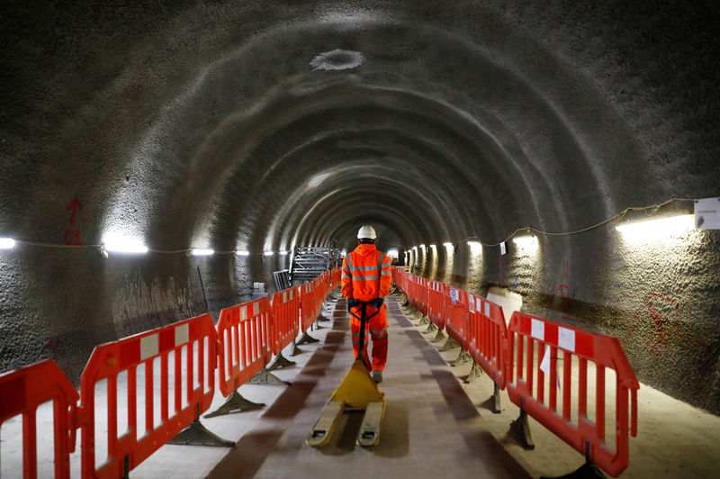 © Reuters. FILE PHOTO: A construction worker drags a trolley down a tunnel at the site for the new Crossrail station in Tottenham Court Road, in London