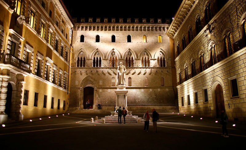 © Reuters. People stand in front of Monte dei Paschi bank headquarters downtown Siena
