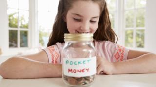 Girl saving her pocket money (posed by model)