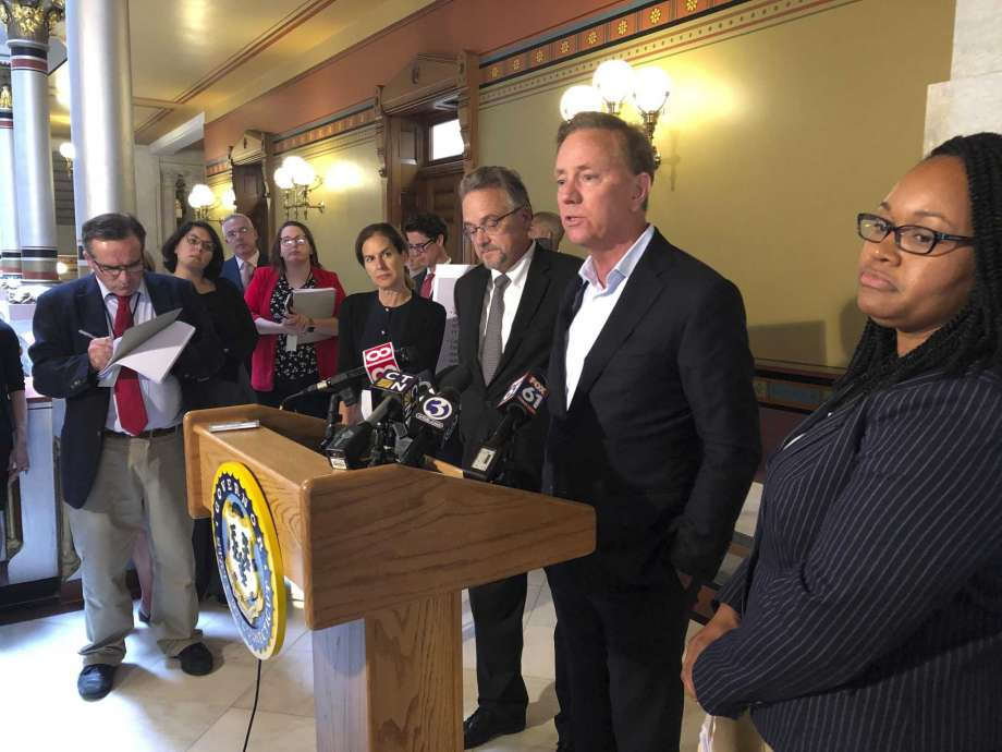 Connecticut Gov. Ned Lamont, center, speaks to reporters at the state Capitol following a closed-door meeting with state lawmakers about electronic tolls on June 19 in Hartford. Lamont says he still hopes to hold a vote on tolls in a special legislative session, despite resistance from some lawmakers. Photo: Susan Haigh / Associated Press / Copyright 2019 The Associated Press. All rights reserved.