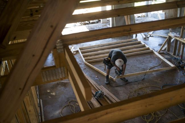 © Bloomberg. A worker saws a section of lumber inside a home under construction at the M/I Homes Inc. Bougainvillea Place housing development in Ellenton, Florida, U.S., on Thursday, July 6, 2017.
