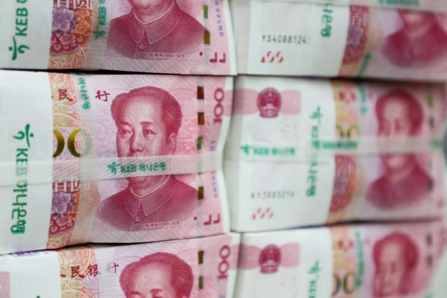 © Bloomberg. Genuine bundles of Chinese one-hundred yuan banknotes are arranged for a photograph at the Counterfeit Notes Response Center of KEB Hana Bank in Seoul, South Korea, on Friday, July 13, 2017. Yuan is set to slide for fifth week, longest losing streak since July 2016, as escalating U.S.-China trade tensions weigh on sentiment.