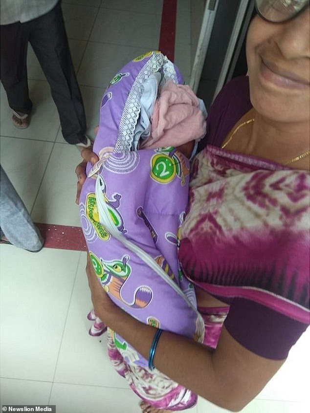 A younger female family member cradles one of the newborn girls after the birth inGuntur city