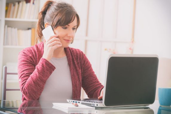 woman on phone and laptop