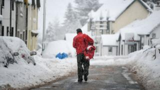 Post man delivering post in the snow.