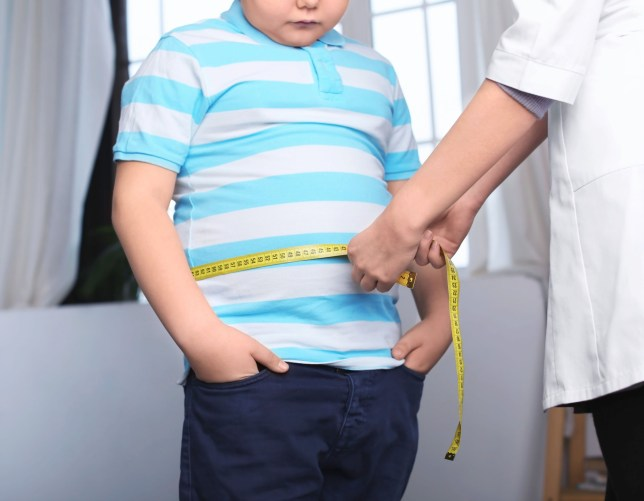 Doctor measuring overweight boy in clinic; Shutterstock ID 1219075759; Purchase Order: -