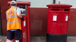 Postman empties letter box