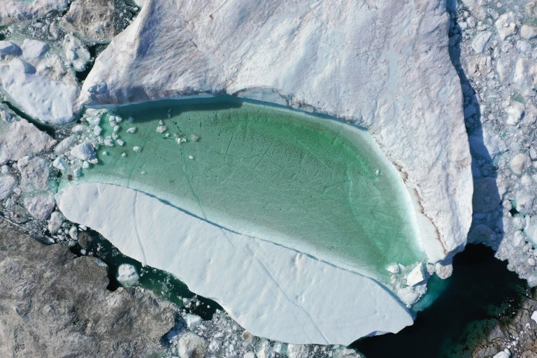 ILULISSAT, GREENLAND - JULY 30: In this aerial view melting ice forms a lake on free-floating ice jammed into the Ilulissat Icefjord during unseasonably warm weather on July 30, 2019 near Ilulissat, Greenland. The Sahara heat wave that recently sent temperatures to record levels in parts of Europe is arriving in Greenland. Climate change is having a profound effect in Greenland, where over the last several decades summers have become longer and the rate that glaciers and the Greenland ice cap are retreating has accelerated. (Photo by Sean Gallup/Getty Images)
