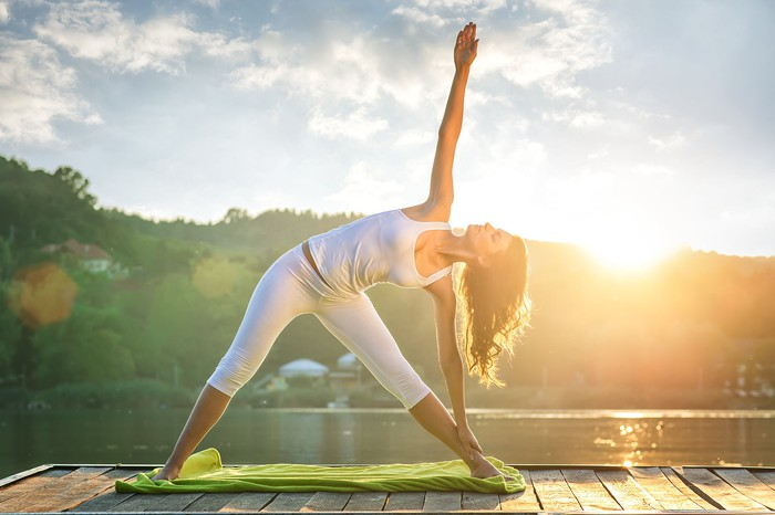 A woman holds a yoga pose by a lake.