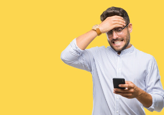 A man slaps his head as he gazes at his smartphone.