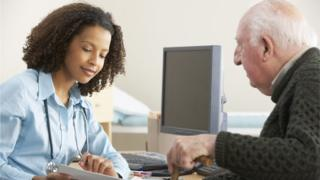 GP talking to older male patient