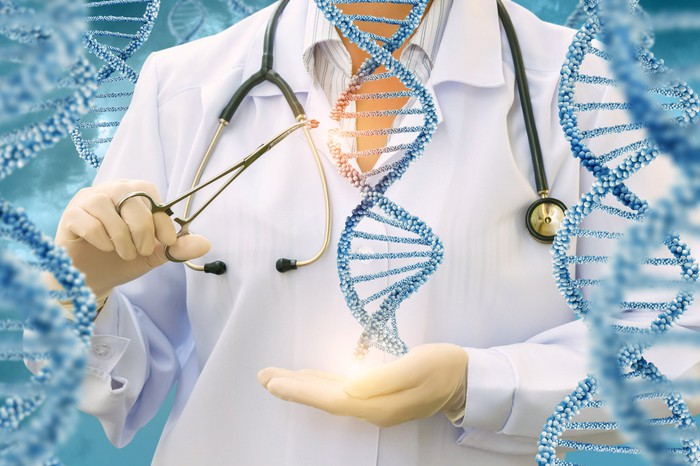 A person in a white coat uses scissors to snip an image of DNA.
