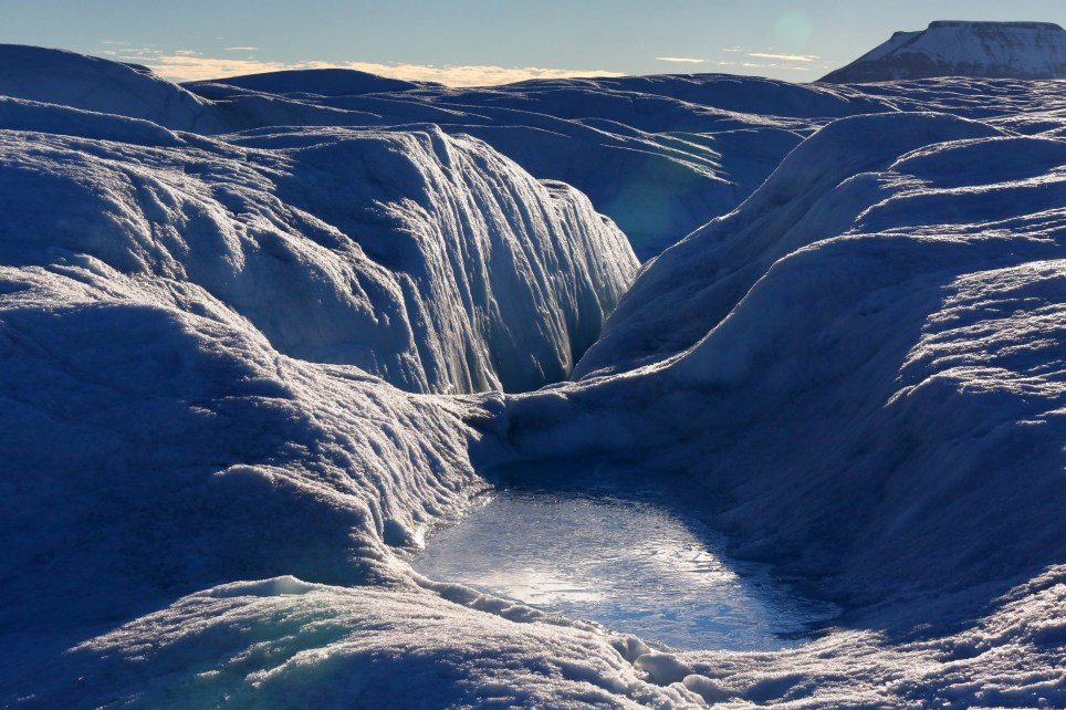 PETERMANN GLACIER, GREENLAND - AUGUST 27, 2016 A pool of frozen water rests on the bumpy, often wet surface of Petermann glacier on August 27, 2016. Petermann's ice shelf broke off a piece roughly four times as large as Manhattan in 2010, and then another the size of two Manhattans in 2012. The shelf had by then lost 23 miles of its prior length, reaching a record low size. Petermann is one of Greenlands most enormous glaciers, lodged in a fjord that, from the height of its mountain walls down to the lowest point of the seafloor, is deeper than the Grand Canyon. And this ice shelf is its frontal extension, spreading out over the half mile or more deep waters of the fjord and actually afloat. The shelf is shrinking, and not quietly when ice shelves go, they can lose huge city-sized chunks at a time.The data stations the scientists installed there the year before are studying how quickly the glacier's ice shelf is melting. They installed a cable from the surface of the glacier down to the bottom of the ocean at the station. The cable has five ocean sensors attached to it that measure things like temperature and salinity, which indicate melt rates. But the station stopped transmitting data about six months ago, and the scientists did not know why until they reached it today. The data was still there, capturing regularly every few hours. The problem was that the Iridium stopped working even though data was still recording. The scientists will work through the night to try to repair the station and restart transmission. From Greenland to Antarctica, disappearing ice shelves have been one of the leading indicators of climate change and Greenland, melting faster than its larger southern rival, now has just a few shelves like Petermann left. The scientists worked on Petermann for about 30 hours, skipping sleep to work through the night, before taking off again. Photo by Whitney Shefte / The Washington Post via Getty Images