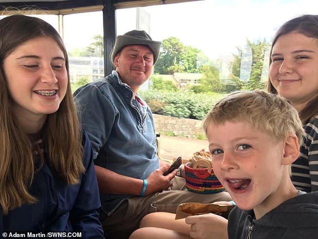 Mr Martin, pictured with his children (from left) Holly (14), George (7) and Megan (15) had to have a total of 12 hours of surgery to repair his heart and artery