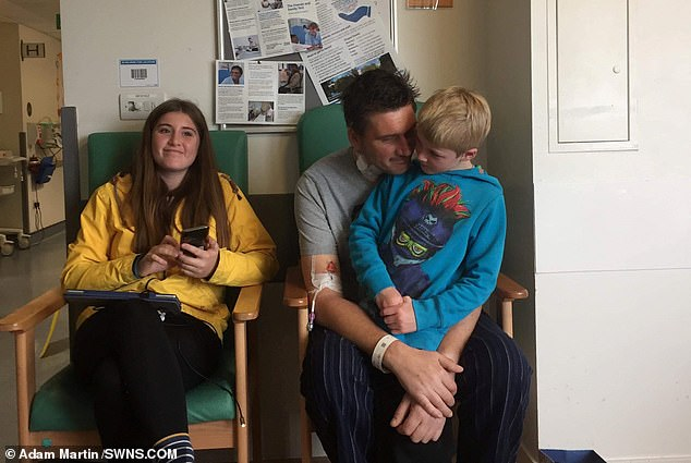 Mr Martin is pictured with two of his children at the hospital in Plymouth, some 80 miles away from his home, where he was taken for his lifesaving surgery