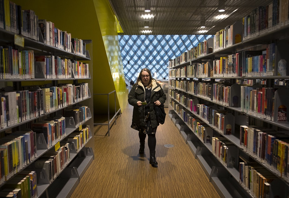 Kara Peters walks through the Seattle Public Central Library to her desk before starting her shift on Wednesday, January 22, 2020, in Seattle.