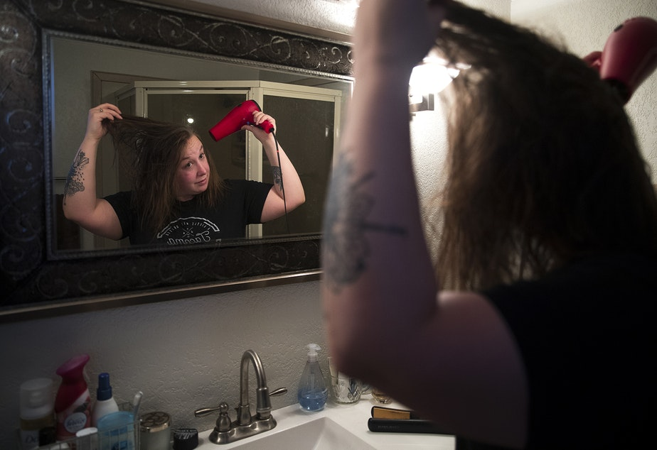 Kara Peters blow dries her hair while getting ready for work on Wednesday, January 22, 2020, at her home in Tacoma. Peters commutes by bus from Tacoma to her job at the Seattle Public Central Library.