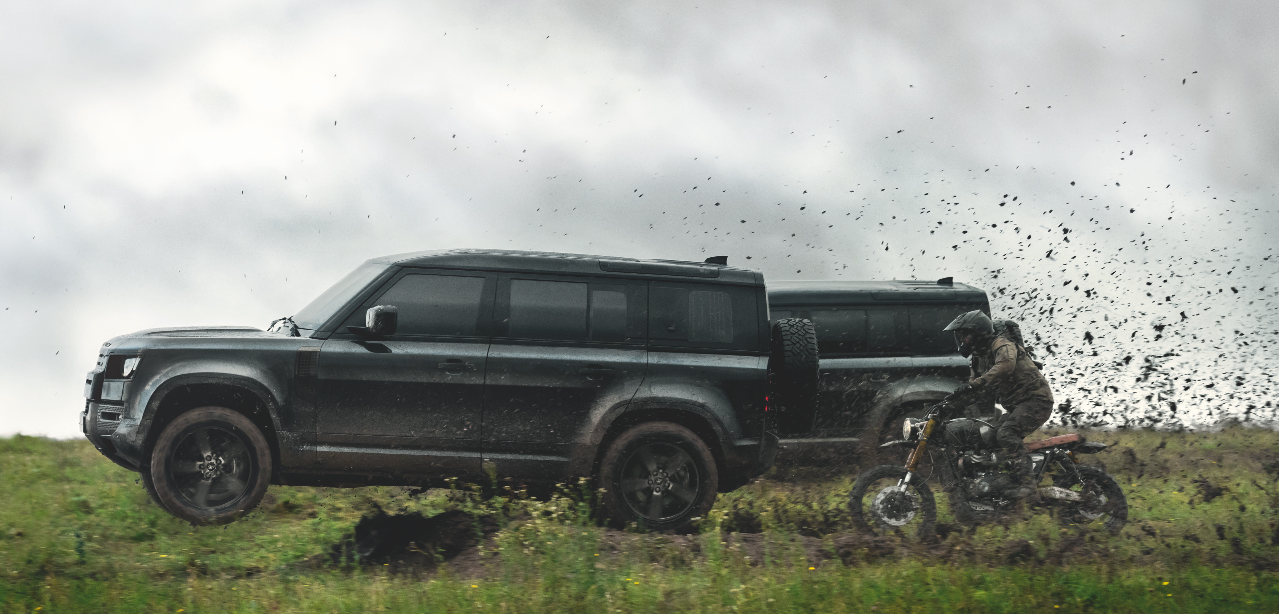The all-black vehicle speeds through a muddy field in the promotional video