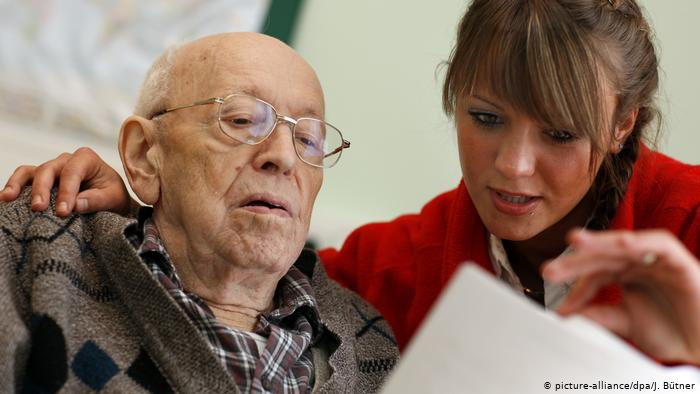 Pensioner next to a woman helping him