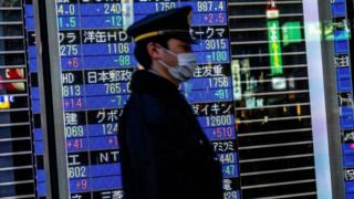 A passerby with a face mask walks past a stock board in Tokyo's Nihonbashi district showing the Nikkei average index falling on the Tokyo Stock Exchange.