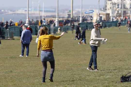 People enjoy the sunshine on the seafront at Brighton as the coronavirus death rate continue to rise