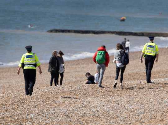 Police Officers ask people who were sitting on the beach at Brighton in West Sussex to leave