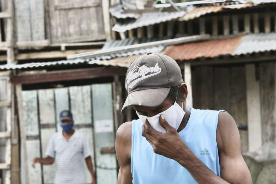 A man wearing mask against the spread of the new coronavirus coughs as he walks in the Cristo del Consuelo neighborhood of Guayaquil, Ecuador, Tuesday, April 14, 2020. The poor neighborhood of Cristo del Consuelo has been hit hard by the new coronavirus pandemic, prompting the local government to provided food and medical assistance for the residents. Photo: Angel De Jesus, AP / Copyright 2020 The Associated Press. All rights reserved