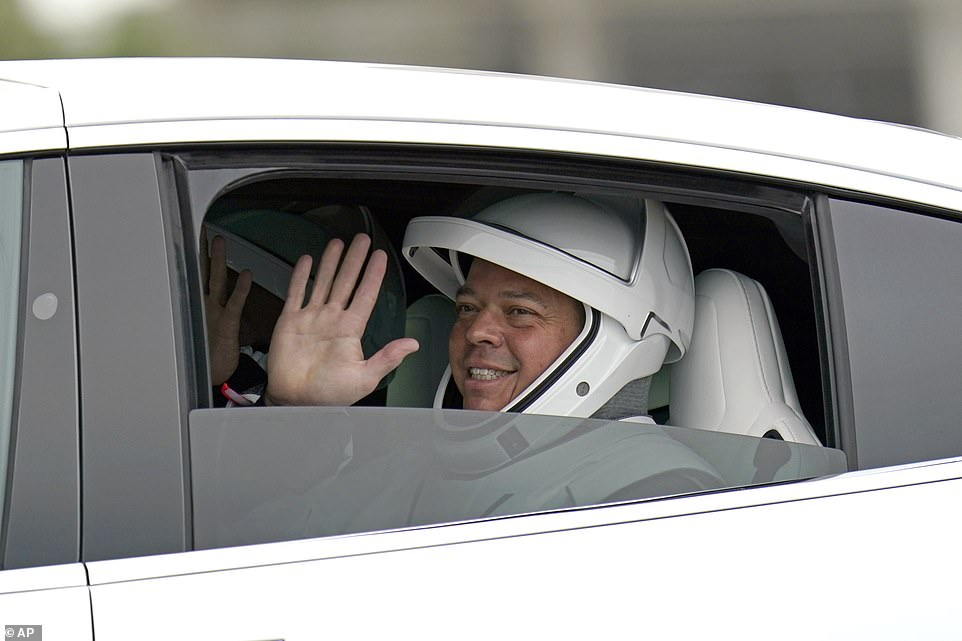 NASA astronaut Bob Behnken waves to the crowd as he and fellow crew member Doug Hurley ride back from Launch Complex 39A after the missions was scrubbed due to bad weather