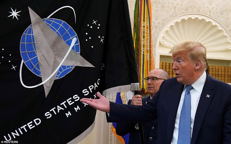 President Donald Trump gestures towards the U.S. Space Force flag during a presentation of the flag in the Oval Office of the White House in Washington, U.S., May 15, 2020. He was in Florida to catch a glimpse of the Falcon 9 launching from Kennedy Space Center