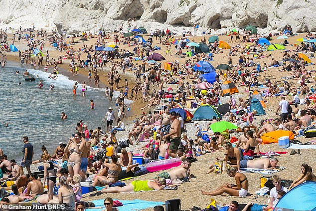 As part of the easing of lockdown restrictions, 2.2 million vulnerable people will be able to go outside with members of their household, while continuing to follow social distancing guidelines. Pictured:Visitors and sunbathers flock to Durdle Door at Lulworth in Dorset on a scorching hot sunny day